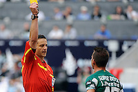 Referee Steven Depiero issues a yellow card to Joao Pereira (47) of Sporting Clube de Portugal. Tottenham Hotspur F. C. and Sporting Clube de Portugal played to a 2-2 tie during a Barclays New York Challenge match at Red Bull Arena in Harrison, NJ, on July 25, 2010.