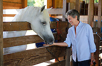 NWA Democrat-Gazette/DAVID GOTTSCHALK - Vickie Kelley, founder and outreach of Natural State Burial Association, gives a treat to one of the Arabian horses on the property of Don Austin off of Hamestring Creek Road in Fayetteville Thursday, July 16, 2015. The 20 acres of property will become a natural burial cemetery.