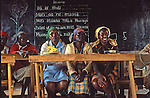 Adult Kikuyu women in Kenya participate in Swahili literacy class with home constructed desks