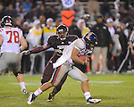 Ole Miss' Barry Brunetti (11) is chased by Mississippi State defensive lineman Devin Jones (60)  in Starkville, Miss. on Saturday, November 26, 2011.