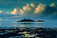 A secluded private island surrounded by smooth glassy water stands dark at sunset beneath large puffy white clouds. Fiji Islands, South Pacific.