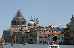View along Grand Canal, showing scaffholding and ship passing on other side of lagoon, Venice, Italy.