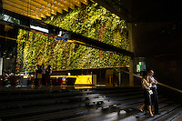 "People walk past the ""Rainforest Rhapsody,"" a 2000 square foot indoor vertical garden installed in the lobby of Six Battery Road that contains 120 plant species. In Singapore, skyrise greenery helps to reduce the urban heat island effect, contributing to the city beautification efforts and bringing nature back into its skyscraper office buildings in the central business district. Photo by Suzanne Lee/Panos Pictures"