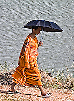 A young monk goes about his daily duties, his umbrella providing a shield from the heat of the midday sun. (Photo by Matt Considine - Images of Asia Collection)