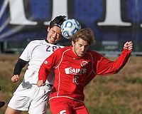 Amherst defender Justin Aoyama (26) and St. Lawrence forward Morgan Smith (15) battle for head ball.  NCAA Division III Sectionals. In double-overtime, Amherst College (white) defeated St. Lawrence University (red), 2-1, on Hitchcock Field at Amherst College on November 23, 2013.