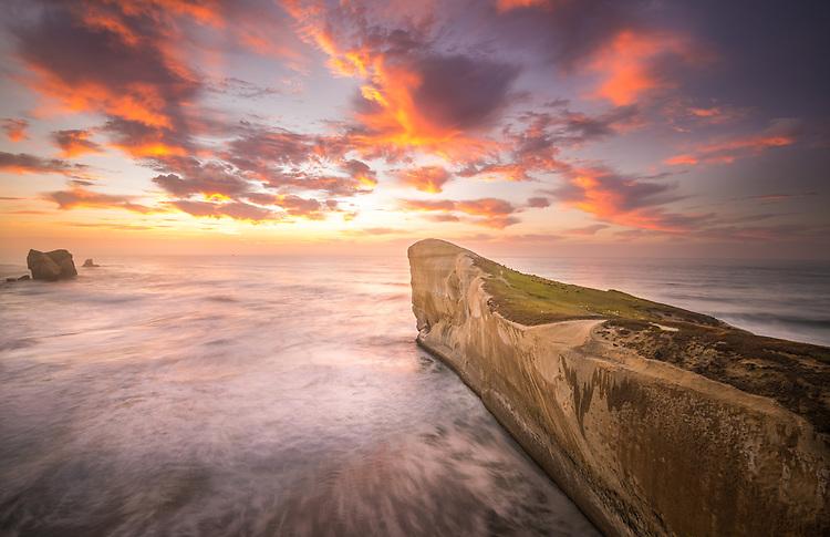 Vivid red sunset in the sky above Tunnel Beach, Dunedin New Zealand - stock photo, canvas prints, fine art print