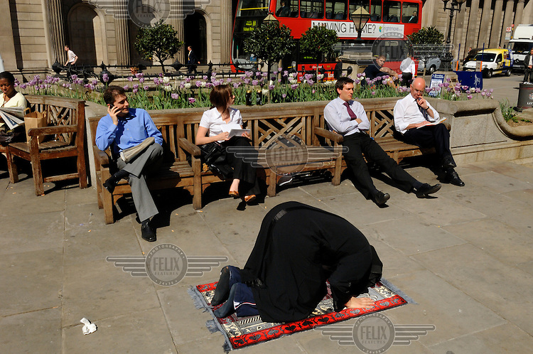 A Muslim prays while others enjoy the lunchtime sunshine in London, by the Bank of England.
