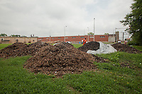 Samuel Soto inspects compost in the ninety-day pile. After decomposing in the thirty-day pile with the ventilation system, inmates transfer the compost to these piles, where it remains for ninety days before undergoing filtration.