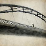 A man crossing a bridge on a raining day