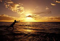 Throw net fisherman frames the sun with his net at Kihei, Maui,