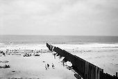 Tijuana, Mexico<br /> August 19, 2007<br /> <br /> The Mexican US border fence dives into the sea on a beach. The beach is split in two by the barrier. The US side is only open to the public on the weekends and people come out to talk with Mexicans through the fence. <br /> <br /> The Mexican beach is always full of life while the US beach is often deserted. Music, children, food, and vendors cover the beach. Mexicans pass back and forth playfully through the barrier under the watchful eye of a border patrolman not far away.<br /> <br /> Signs on the US side warn of the polluted waters that the US says comes from a waste treatment plant on the Mexican side.