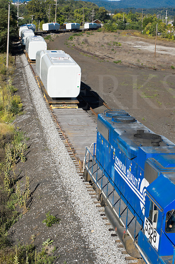 Hollidaysburg, Pennsylvania, USA - September 14, 2010: Wind turbine nacelles loaded on flatcars being moved by railroad train away from assembly plant, manufacturing and distribution of large parts for alternative energy.