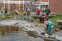 Grundschulklasse, Schulklasse legt einen Schulteich, Schul-Teich, Teich, Gartenteich, Garten-Teich im Schulgarten an, der Uferbereich wird mit Feldsteinen ausgelegt, eingefasst