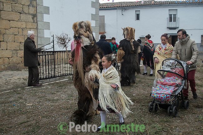 "A Carantoña walks with her girl  during the Carantoñas festival, in Acehúche near Cáceres, on January 21, 2015. The ""Carantoñas"", monster-animal characters mixing paganism with Christianity, search for Saint Sebastian in the streets of the village of Acehúche, southwestern Estremadure province, dressed in patchwork sheep, cow, rabbit and goatskins under painted masks. Arriving eventually at the village church, a procession takes place with the statue of the patron saint. Until recently, Spain's neighbors, the Berbers of Morocco, preserved a version of the same ritual in their animal-hided winter ""goblin,"" Bou Inania.  © Pedro ARMESTRE"