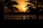 Silhouetted holidaymakers watching the sun go down. Los Cristianos,Tenerife, Canary Islands.