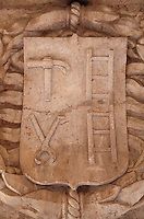 Sculptural detail of a shield with the instruments of the Passion, ladder, hammer and pliers, in the arcade of the Cloister, built in Manueline style by Diogo Boitac, Joao de Castilho and Diogo de Torralva, completed 1541, in the Jeronimos Monastery or Hieronymites Monastery, a monastery of the Order of St Jerome, built in the 16th century in Late Gothic Manueline style, Belem, Lisbon, Portugal. The cloister wings have wide arcades with rectangular column and tracery within the arches. The monastery is listed as a UNESCO World Heritage Site. Picture by Manuel Cohen