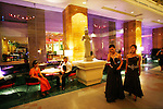 Phnom Penh's Nagaworld Casino and five-star hotel is one of Cambodia's biggest private employers with more than 3,000 staff catering for a stream of visitors. It functions non-stop 24 hours a day with an inside airconditioned controlled temperature of 21 degrees.It is a 14 storey hotel and entertainment complex, with more than 500 bedrooms, 14 restaurants and bars, 700 slot machines and 200 gambling tables. There is also a spa, karaoke and VIP suites, live bands, and a nightclub. Its monolithic building dominates the skyline at the meeting point of the Mekong and Tonle Sap rivers, in stark contrast to nearby intricate Khmer architecture.///Entrance lobby to Nagaworld with statues and guests