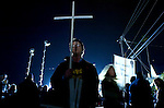 A protester holds up a cross as he protests outside San Quentin Prison, the night before the execution of Stanley Tookie Williams, Monday Dec. 12, 2005..Sacramento Bee/ Brian Baer.