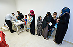 Dr. Saba Ghawi, a pediatrician, examines a young patient as others wait their turn in a clinic in Madaba, a sprawling Palestinian refugee camp in Jordan that has grown in recent years with the arrival of refugees from war-torn Syria. The clinic is run by the Department of Service for Palestinian Refugees of the Middle East Council of Churches, a member of the ACT Alliance. <br /> <br /> Parental consent obtained.