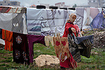 "A woman refugee from Syria puts her laundry out to dry. She lives with her family in a rented ""tent""--made from a billboard canvas of a dollar bill--in the village of Jeb Jennine, in Lebanon's Bekaa Valley. They and other refugee families in the area are being assisted by International Orthodox Christian Charities and other members of the ACT Alliance.."