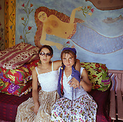 Two Kalderash Roma girls in front of a hand painted mural depicting a mermaid, n a house in the old part of the Roma camp of Sintesti. The camp is home to approximately 1000 Roma..