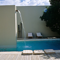 The water of the outdoor swimming pool is replenished continuously from a chute at the top of the wall