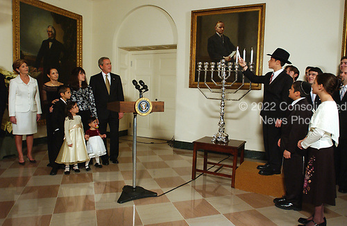 For the past three years, the President has participated in a Menorah lighting before the annual White House Hanukkah Reception.&nbsp;At right, Menachem Felzenberg lights the Chanukah Menorah as his siblings, Chaim, and Miriam look on, three of the six Felzenberg children.&nbsp; At left are United States President George W. Bush and first lady Laura Bush with the rest of the Felzenberg family.  Their father, Captain Shmuel Felzenberg, is serving in Iraq as the senior Jewish chaplain with the United States Army's 84th Engineer Battalion, from Schofield Barracks, Hawaii. Captain Felzenberg is scheduled to return home in January.  The four-foot-tall sterling silver Menorah is on loan from the Boca Raton Synagogue in Boca Raton, Florida. The Menorah was made in Israel and purchased for the synagogue by two congregants, Nachman and Jamie Feig.&nbsp;Because tonight is the third night of Chanukah, the lighters will light three candles and the shamash, the main candle. <br /> Credit: Ron Sachs / Pool via CNP