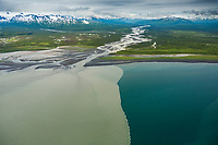 The water from a glacially fed river along Alaska's southwest coast mixes with the blue sea water, Alaska Peninsula. Aleutian mountain range in the distance.