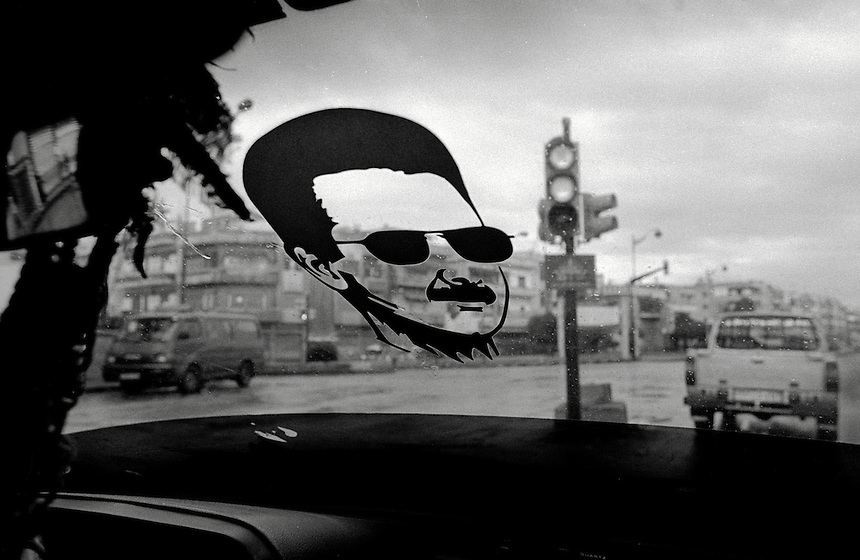 A silhouette of Syrian President Bashar al-Assad watches the street from the windscreen of a taxi in Homs, Syria, November 2008. Photo: Ed Giles.