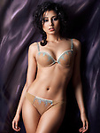 Young glamorous woman wearing beige lingerie on dark flowy fabric background