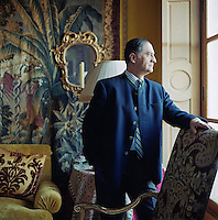 Portrait of interior designer Alidad Mahloudji standing and looking out of the window of a Parisien home he designed