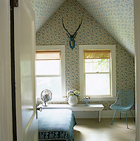 The walls of this attic guest bedroom are covered in a floral cotton fabric and the bed cover is of Indian batik with a 1960s blue wire chair in the corner under the eaves