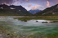 A moody view at sunset of the Grivola , one of the highest peaks (3900 meters)of the Gran Paradiso range, with a bend of the Savara river in the foreground. Stitched from four verticals