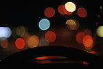 Rush hour traffic looking through windshield at cars break lights in rain with steering wheel Seattle Washington State USA.