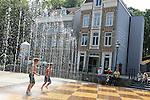 Foto: VidiPhoto<br /> <br /> ARNHEM - Kinderen vermaken zich donderdag in de nieuwste aanwinst van het Nederlands Openluchtmuseum in Arnhem, de Play Fountain. Het betreft een proefopstelling van Ice World, de leverancier van ijsbanen. Het bedrijf wil nu ook 'zomers vermaak' gaan verzorgen en heeft daarom in Nederland twee proefopstellingen geplaatst van de speelfontein. Een daarvan staat nu in Arnhem. De Play Fountain is gebaseerd op de Bedriegertjes van kasteel Rosendael, alleen gaat hier het water onverwachts spuiten op de maat van de muziek. Voordeel voor het Openluchtmuseum is dat mensen nu ook het park bezoeken bij warm weer. De fontein blijkt een groot succes, vooral bij kinderen.