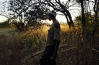 Yaeda Valley, Tanzania: Gonga Gonga, a Hadzabe man, heads out to hunt in the hills surrounding this valley in Northern Tanzania. The Hadzabe, one of the last tribes of hunter gatherers in the world, are the second oldest people in human history. DNA testing has traced them back 60,000 to 90,000 years, and their habits have changed relatively little since then. Gonga wears clothes now, but he also hews his own arrows using his teeth. (PHOTO: MIGUEL JUAREZ LUGO)