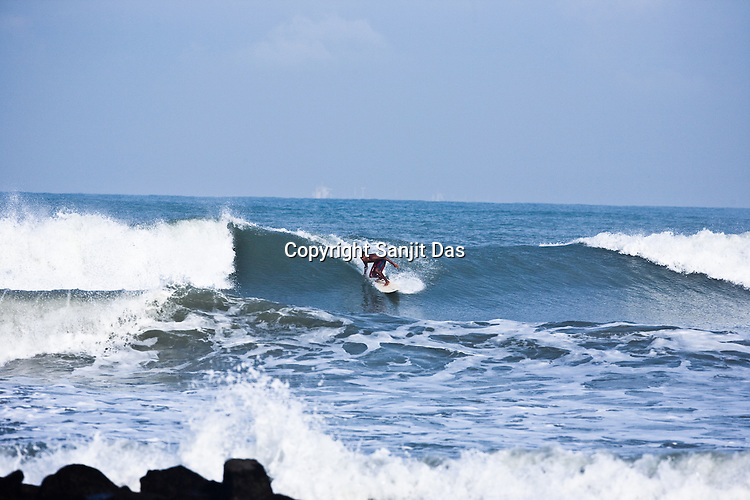 """Kirtan Ananda, one of the Krishna devotees from the Kaliya Mardana Krishna Ashram is seen surfing on the Arabian Sea on the beach front of Mangalore, Karnataka, India.  ..Krishna devotees in the Gaudiya Vaishnava tradition of Hinduism, they are known collectively as the """"surfing swamis."""" The """"surfing ashram"""" is growing in popularity and surfing here is a form of meditation, a spiritual practice leading to heightened states of awareness."""