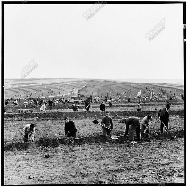 """""""Educated youth"""" and local peasants of the Xingan production brigade work on an arid field's terrace irrigation system. Xinsheng commune, Baiquan county, 10 November 1975"""