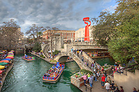 The Torch of Frienship, a gift from Mexico to San Antonio, Texas, stands above the Riverwalk on a pleasant Spring afternoon. Along the San Antonio River, the boats take tourists through the canals, a brief respite from the crowded sidewalks.