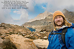 A smiling male hiker with granite mountain landscape and swirling clouds behind him.<br />