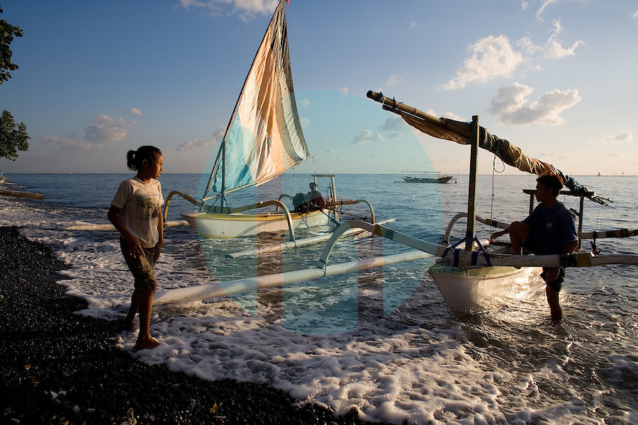 September 9th 2007- Bali, Indonesia- Fisherman return at sunrise after a nights fishing in an area known as Jemeluk Bay, which is located near the Amed area of North East Bali. The area around Amed is very dry and not suitable for rice, so the local population depends heavily on the tourism trade. That has helped the dive operators ink deals with local villagers to protect the in-shore reefs, with fishermen promising to drop their lines out at sea. The dive shops pay monthly dues to the villages and pay to use local porters to carry tanks and boats to reach the sites. Photograph by Daniel J. Groshong/Tayo Photo Group