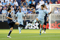 Davide Chiumiento (navy) Vancouver Whitecaps and Graham Zusi (8) Sporting KC challenge for the ball in midfield... Sporting KC defeated Vancouver Whitecaps 2-1 at LIVESTRONG Sporting Park, Kansas City, Kanas.