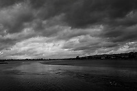 Storm clouds in black and white hover over San Leandro Bay at MLK Regional Park in Oakland.