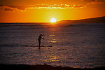 Enjoying the brilliant and warm colors of a hawaiian sunset from Magic Island on Oahu. A paddle boarder goes by. A couple sit close to each other.