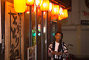 A young lady waiting to meet a friend outside a restaurant in the evening, in Nagoya Japan.