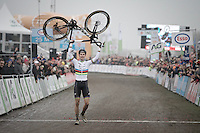 Wout van Aert (BEL/VerandasWillems-Crelan) walking over the finish line holding his new bike sponsor high as he becomes Belgian National Elite Cyclocross Champion for a 2nd time in a row<br />