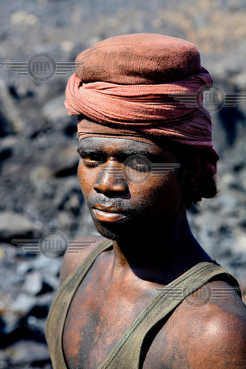 The face of a contract labourer, working at an open cast coal mine, coated in thick black coal dust. After carrying baskets of rock coal for 10 - 12 hours per day he'll earn less than GBP 2.20. /Felix Features