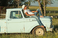 cowboy relaxing on top of an old truck on a ranch