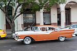Havana, Cuba; a classic orange and white 1957 Ford Fairlane driving along the Paseo de Marti past the Saratoga Hotel