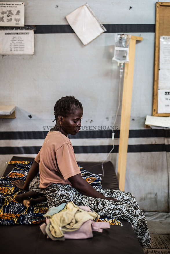 CAR,Bangui:  A mother is staying next to her child that has high fever. The child is treated in the MSF clinic of Mpoko that hospitalize the patients if needed. If the case become very bad, they transfer them to another hospital in the city.  21th April 2016.<br /> <br /> RCA: une m&egrave;re est assise &agrave; cot&eacute; de son enfant qui a de la fi&egrave;vre. L'enfants est trait&eacute; dans la clinique MSF de Mpoko qui hospitalise les patients si besoin. Si la cas devient grave, ils transmettent les patients vers un autre h&ocirc;pital de la ville. 21 avril 2016